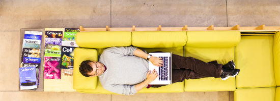 man laying on a yellow couch typing on a laptop